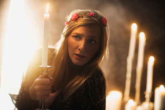 Sorceress holding candle in dark room