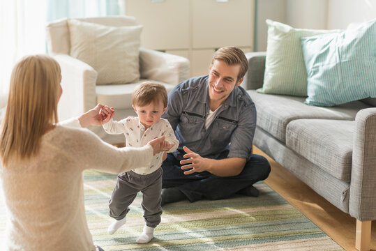 Happy parents helping little son (2-3 years) walking in living room
