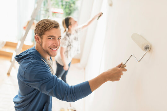 Smiling couple painting wall