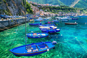 Colorful fishing boats and transparent emerald sea of Calabria. Scilla town. Italy