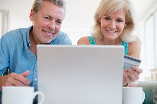 Portrait of couple using laptop, with credit card in view