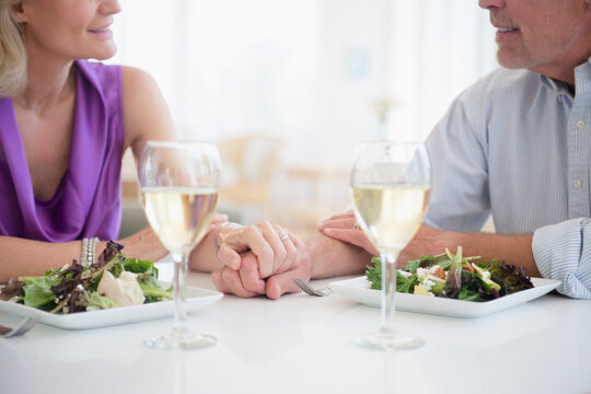Cropped view of couple holding hands in restaurant with glasses of white wine in foreground