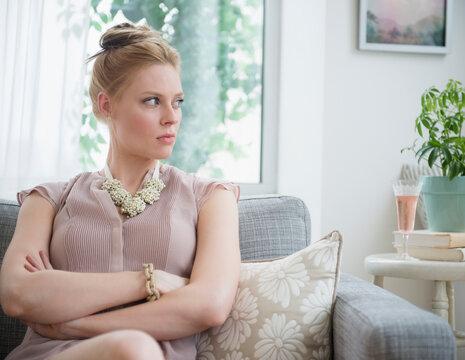 Upset young woman sitting on sofa