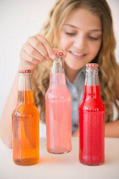 Girl (12-13) and three soda bottles