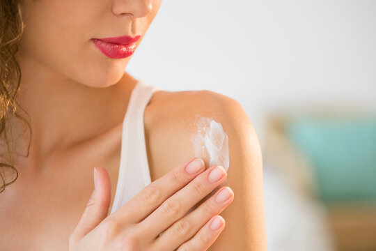 Young woman applying cream on shoulder