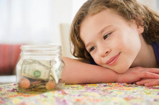 Girl (10-11) girl looking at jar full of money