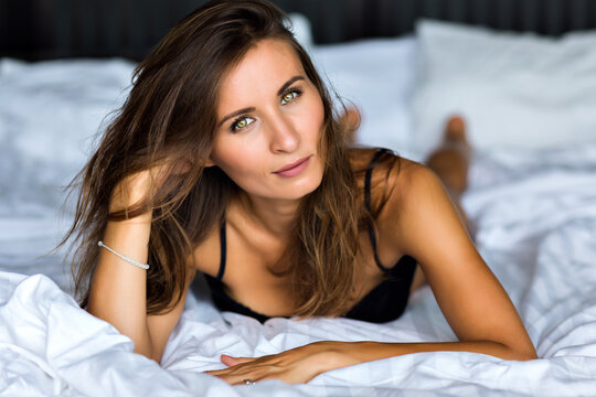 Lifestyle close up portrait of magnificent beautiful brunette woman, perfect skin, natural make up, olive eyes, tanned skin, soft pastel color, relax at her barroom, wearing lingerie, morning time.