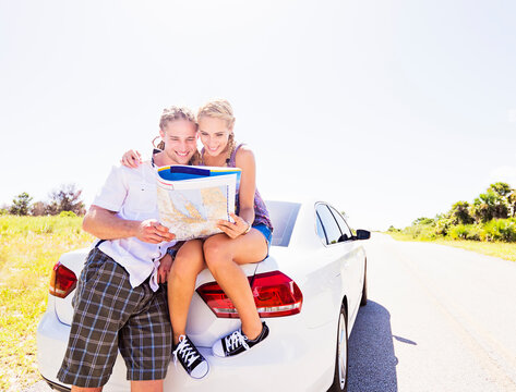 Couple at back of car looking at map
