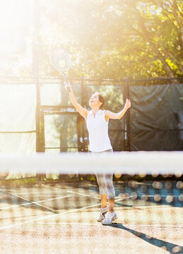 Young woman in tennis court about to serve ball with net in blurred foreground