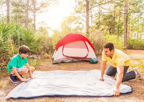 Father and son (12-13) preparing sleeping bag for camping