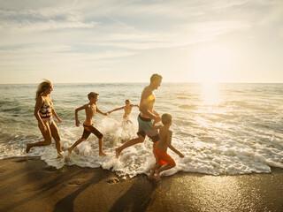 Family with three children (6-7, 10-11, 14-15) running on beach