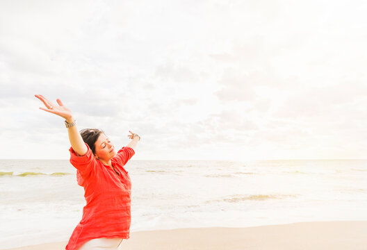 Side view of woman standing with arms up on beach