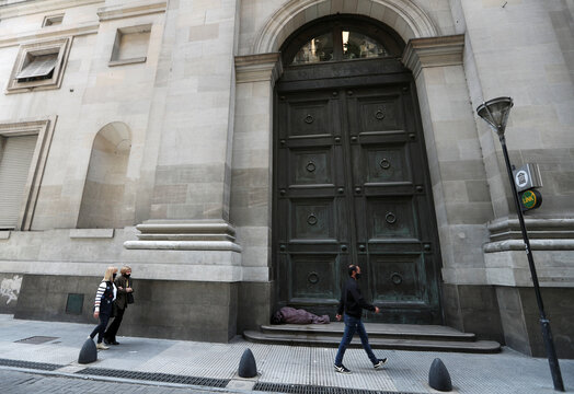 Pedestrians walk by a homeless person sleeping outside Argentina's National Bank, in Buenos Aires' financial district