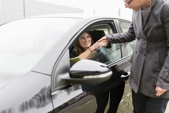 Women shaking hands through open car window