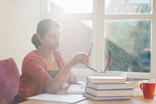 Young woman studying books at desk
