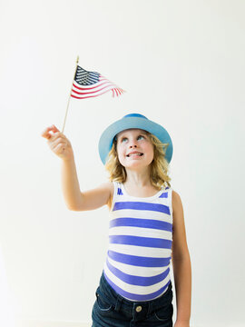 Portrait of blonde girl (4-5) holding American flag