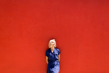 Woman in blue dress posing against red wall in sunlight