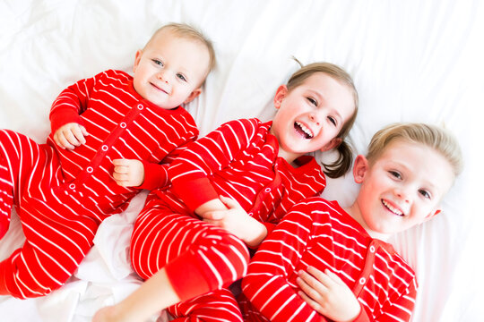 Girl (4-5) and two brothers (6-7) lying on bed in striped pajamas