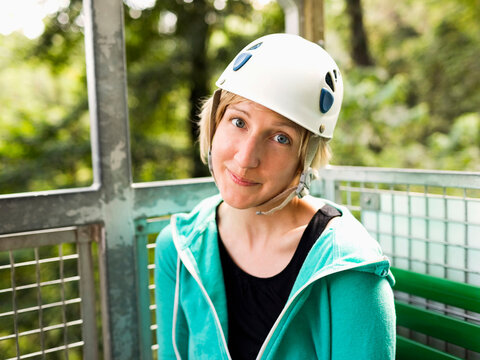 Woman in protective helmet and sitting at net elevator looking at camera