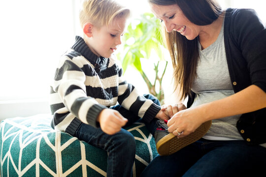 Mother helping son (6-7) putting shoe on