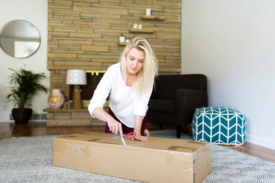 Young woman opening box with scissors