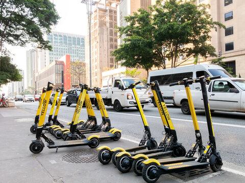 SAO PAULO, BRAZIL - OCT 25, 2019 - Yellow scooters for rent in São Paulo Paulista sidewalk Paulista avenue