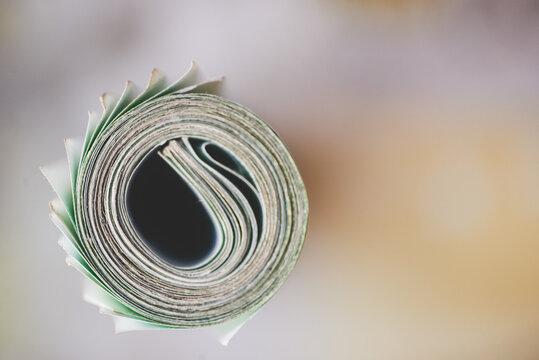 roll of one hundred euro bills against two hundred bills