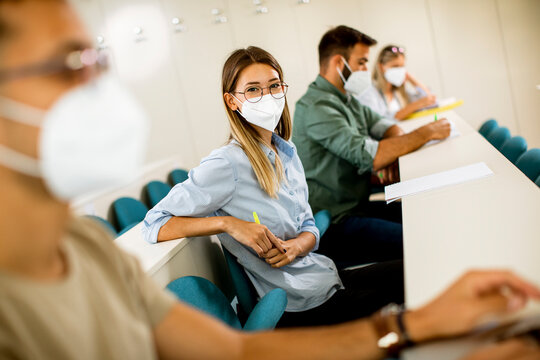 Female student wearing face protective medical mask for virus protection at lecture hall