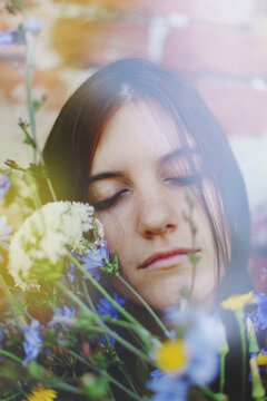 Romantic young woman sleeping with her head on a bed of flowers