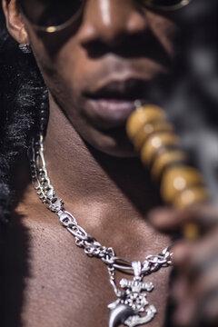black man smokes hookah, detail, dark club atmosphere