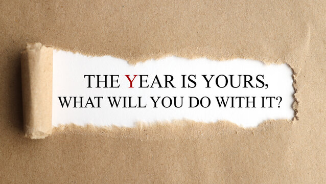 Motivational quote The year is yours. What will you do with it? appearing behind torn blue paper.