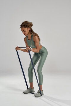 Vertical shot of a young athletic mixed race woman in sportswear standing isolated over grey background and exercising with elastic band or fitness gum