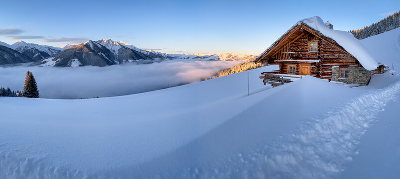 Snow covered mountain hut old farmhouse in the Austrian alps at sunrise against blue sky.