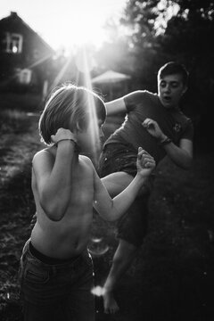 Two boys play fighting at dusk.