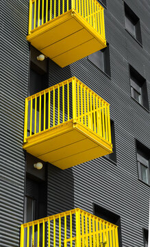 Building detail with yellow balcony on grey/black facade