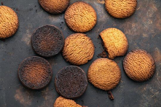 Burnt cookies. Burnt, burnt oatmeal cookies lie on a black baking sheet.