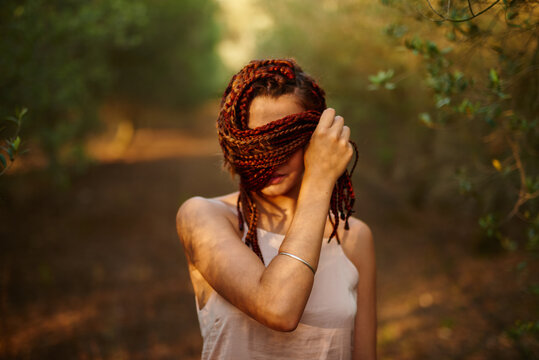 woman cover her face with her braided hair
