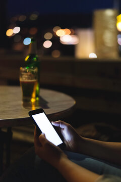 Woman having a beer and looking her smartphone