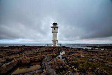 The lighthouse of Iceland with a cloudy sky.