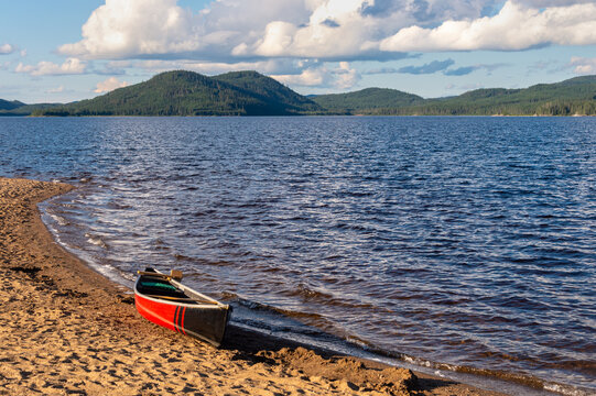 Red & black canoe on a lake shore in Quebec, Canada