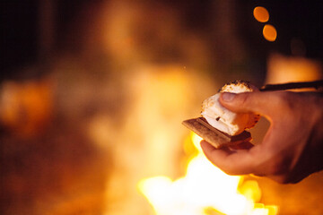 A caucasian hand placing roasted marshmallows on a graham cracker making s'mores.