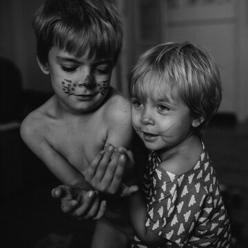 Siblings with painted faces play together.
