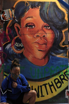 A woman poses in front of a Breonna Taylor mural at Black Lives Matter Plaza in Washington