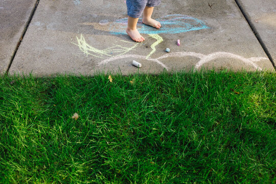 Young boy plays outside with chalk barefoot.