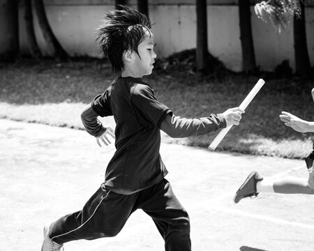 Young kid running the relay race and passing the baton to his teammate