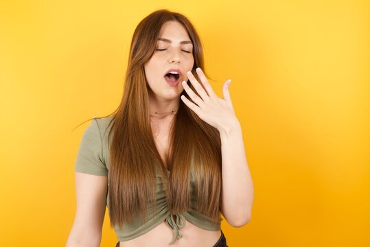 Young caucasian woman with long hair wearing green tshirt standing over isolated yellow background being tired and yawning after spending all day at work.