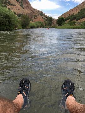 A man's hairy legs riding an inner tube down a river