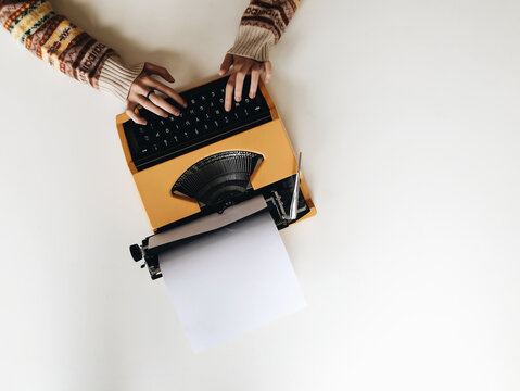 Overhead image of girl typing on yellow typewriter