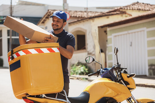 Delivery man taking box out of the bike