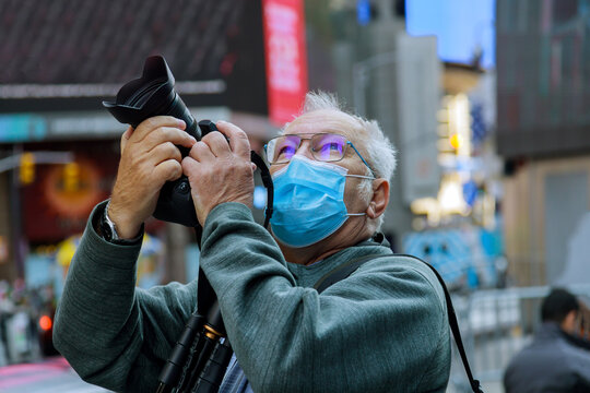 Travelling in American city The new normal tourism with mask middle aged man takes a picture of the New York